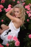Blonde Frau, die unter Rosen sitzt Stockfotografie
