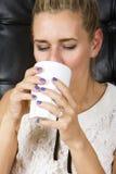 Blonde Frau, die von einer weißen Schale trinkt Lizenzfreie Stockbilder