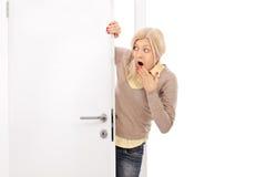 Blonde Frau, die von hinten eine Tür späht Stockbilder