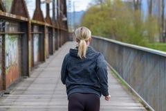 Blonde Frau, die weg über einer alten Brücke rüttelt Stockbilder