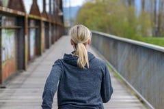 Blonde Frau, die weg über einer alten Brücke rüttelt Lizenzfreies Stockfoto