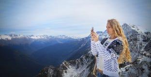 Blonde Frau, die Winterlandschaftsberge fotografiert Stockfoto