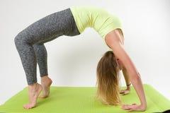 Blonde Frau, die Yoga tut und Übungen ausdehnt Stockfotografie