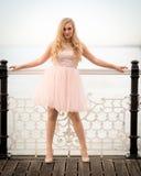 Blonde Frau, die am Zaun Teasing sich lehnt Lizenzfreie Stockfotografie