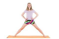 Blonde Frau, die zu den Übungen stehen auf einer Matte sich vorbereitet Lizenzfreie Stockbilder