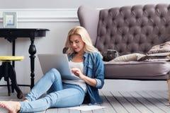 Blonde Frau, die zu Hause mit Laptop arbeitet Lizenzfreie Stockfotos