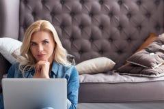Blonde Frau, die zu Hause mit Laptop arbeitet Stockbild