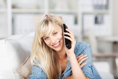 Blonde Frau, die zu Hause nennt Lizenzfreies Stockfoto