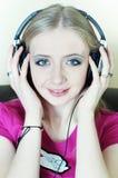 Blonde Frau, die zum Musiklächeln hört Stockfotos