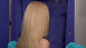 Blonde Frau, die zur Kamera, hereinkommendes cryosauna lächelt stock footage