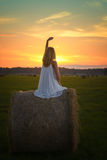 Blonde Frau, die zur Sonnenuntergangzeit auf einem Feld aufwirft Lizenzfreie Stockfotos