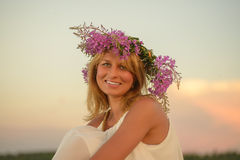 Blonde Frau, die zur Sonnenuntergangzeit auf einem Feld aufwirft Lizenzfreies Stockfoto