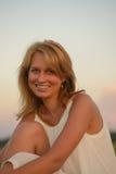 Blonde Frau, die zur Sonnenuntergangzeit auf einem Feld aufwirft Stockfoto