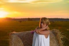 Blonde Frau, die zur Sonnenuntergangzeit auf einem Feld aufwirft Stockfotos