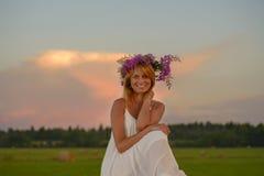 Blonde Frau, die zur Sonnenuntergangzeit auf einem Feld aufwirft Lizenzfreie Stockbilder