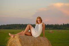 Blonde Frau, die zur Sonnenuntergangzeit auf einem Feld aufwirft Stockbilder