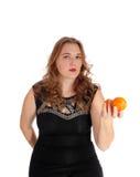 Blonde Frau, die zwei Orangen hält Stockfoto