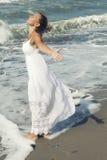 Blonde Frau durch den Ozean und das Verbreiten ihrer Arme Stockbild