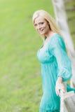 Blonde Frau durch den Zaun Stockfotografie