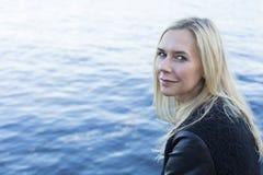 Blonde Frau durch die Ufergegend Lizenzfreies Stockbild