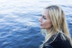 Blonde Frau durch die Ufergegend Lizenzfreie Stockbilder