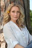 Blonde Frau durch einen Baum Lizenzfreies Stockfoto