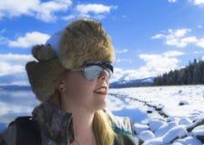 Blonde Frau durch schneebedeckten See in den Bergen Lizenzfreies Stockfoto
