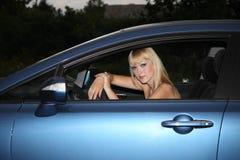 Blonde Frau in einem blauen Auto Stockbilder