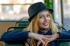 Blonde Frau in einem blauen Hut, der im Bus sitzt Lizenzfreie Stockbilder