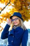 Blonde Frau in einem blauen Hut richtet Gläser gerade Stockfotos