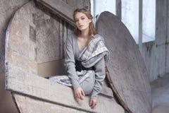 Blonde Frau in einem grauen Kleid Stockbilder