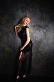 Blonde Frau in einem langen schwarzen Abendkleid Stockfoto