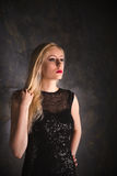 Blonde Frau in einem langen schwarzen Abendkleid Stockbild