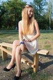 Blonde Frau in einem Park auf einer Bank Lizenzfreie Stockfotos