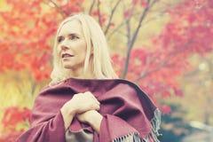 Blonde Frau in einem Park im Herbst Lizenzfreies Stockfoto