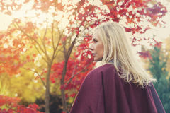 Blonde Frau in einem Park im Herbst Stockbild