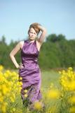 Blonde Frau in einem purpurroten Kleid Stockfotos