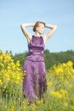 Blonde Frau in einem purpurroten Kleid Stockbild