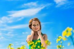 Blonde Frau in einem Rapsfeld Stockfotografie