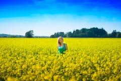 Blonde Frau in einem Rapsfeld Stockfotos