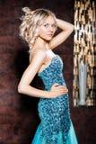Blonde Frau in einem schönen glänzenden Kleid Stockfoto