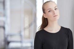 Blonde Frau in einem schwarzen Kleid Stockfotos