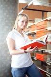 Blonde Frau in einer Bibliothek Stockbilder