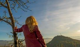 Blonde Frau in einer roten Jacke, die von oben schaut Stockfotografie
