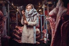 Blonde Frau in einer warmen Jacke in einem Fleischgefrierschrankspeicher Lizenzfreie Stockbilder
