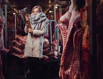 Blonde Frau in einer warmen Jacke in einem Fleischgefrierschrankspeicher Stockfoto