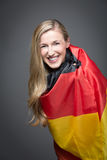 Blonde Frau eingewickelt in der Flagge von Deutschland Stockbild