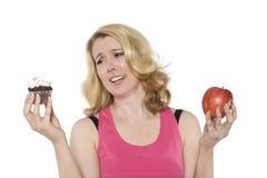 Blonde Frau entscheidet zwischen einem kleinen Kuchen und einem Apfel Stockfotografie