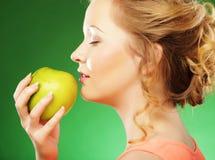 Blonde Frau essen grünen Apfel über grünem Hintergrund Stockfotos