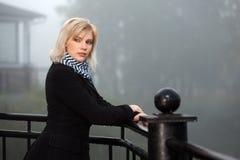 Blonde Frau gegen eine nebelige Landschaft des Morgens Stockbild